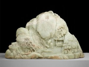 Carved stone sculpture depicting a village scene with a mountain.