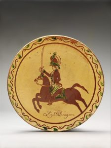 Decorated plate with a painted figure of a man with a sword who is riding a horse.