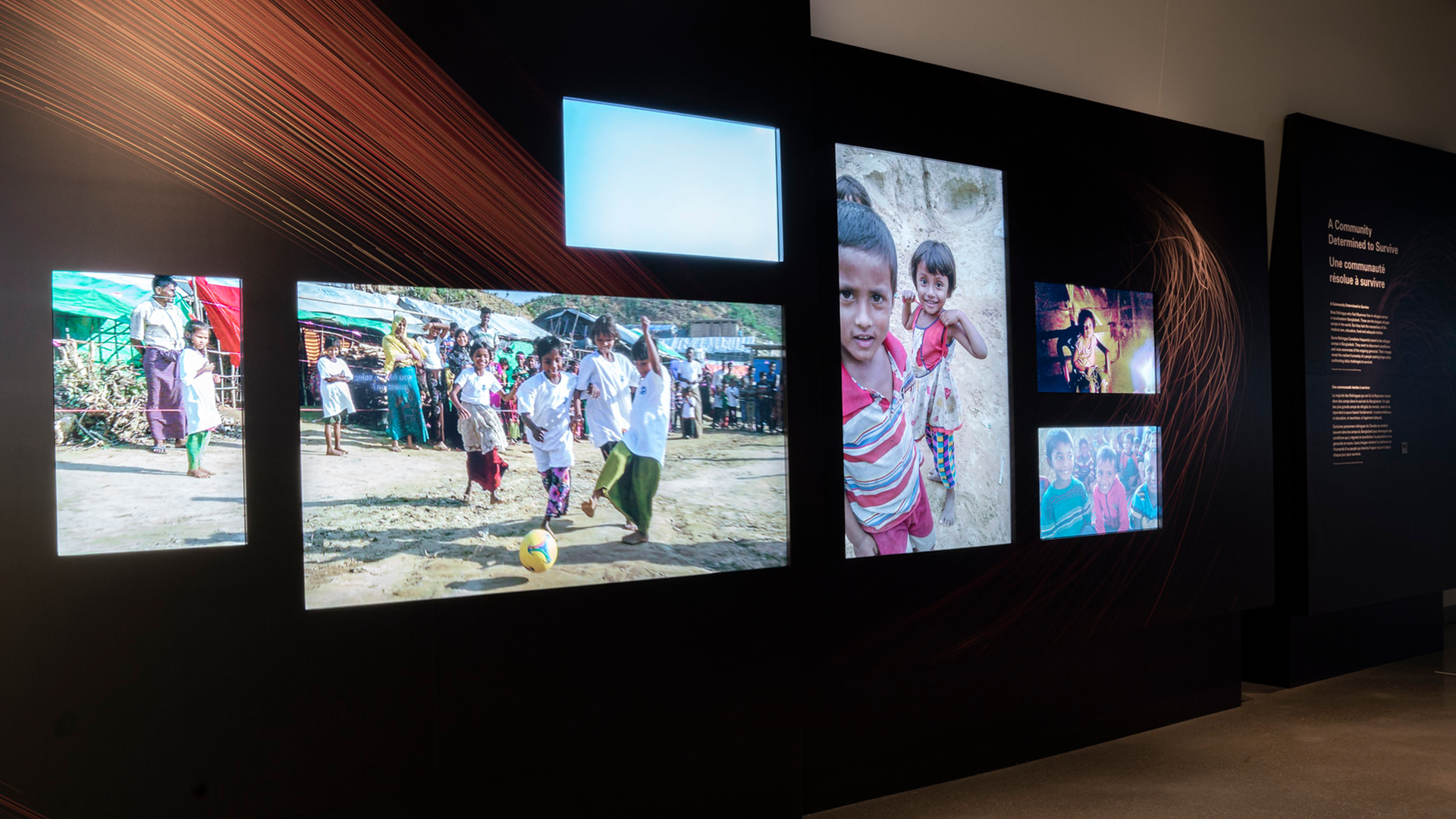 A section of wall with a series of screens in both portrait and landscape orientations are depicting scenes of refugee camps