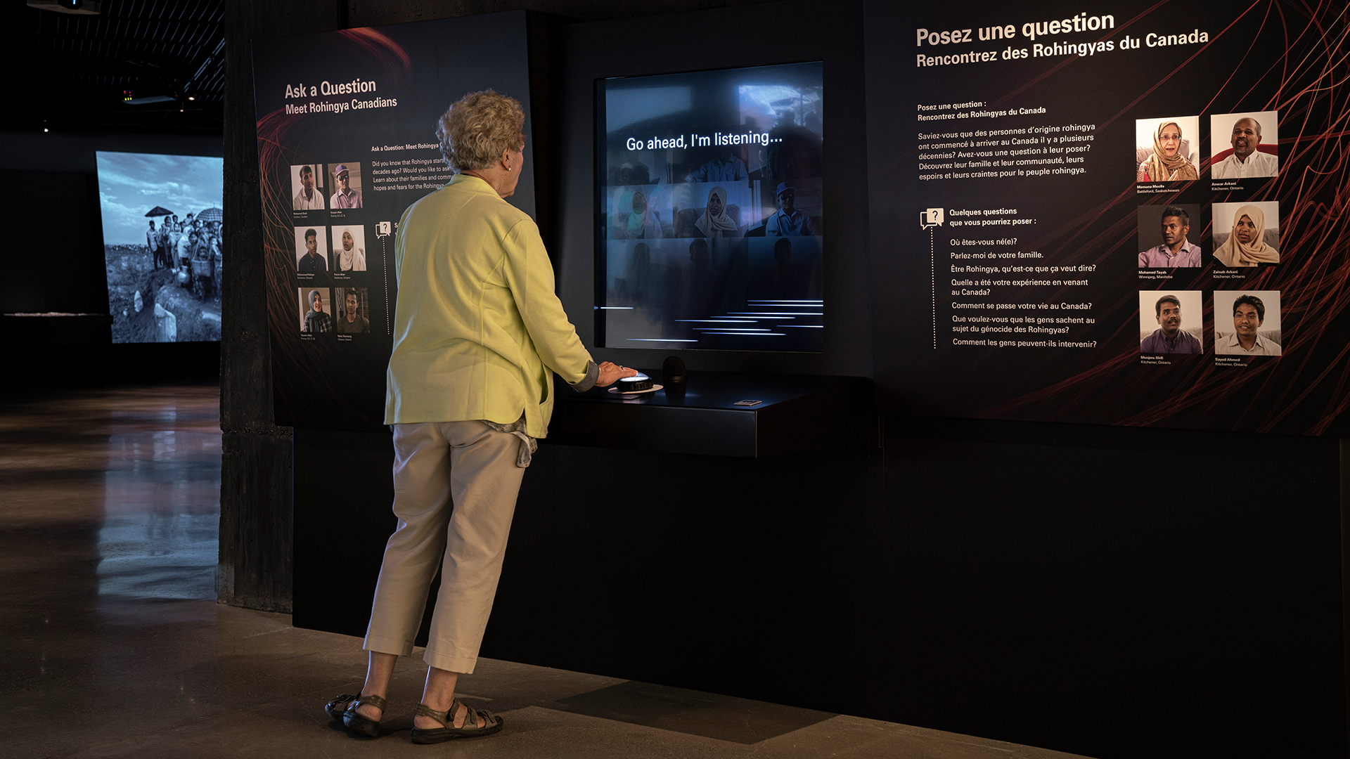 A mature female visitor standing in front of a museum exhibition.