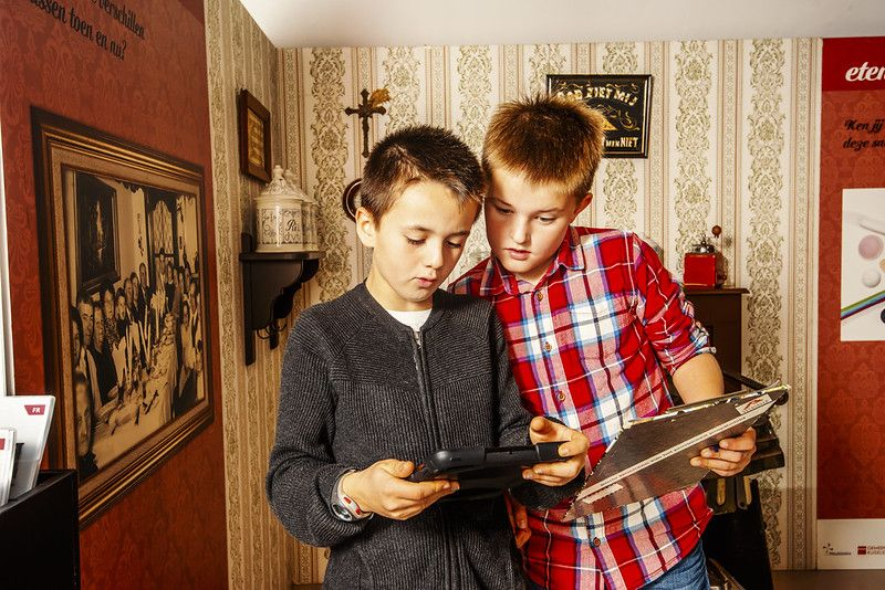two children visiting the Museum of Folk Life, one with an iPad, the other with an old schoolbook