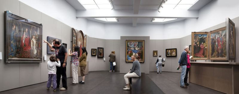 """museum hall in the Groeningemuseum, with the famous painting """"Virgin and Child with Canon van der Paele"""" by Jan van Eyck on the left side of the hall"""