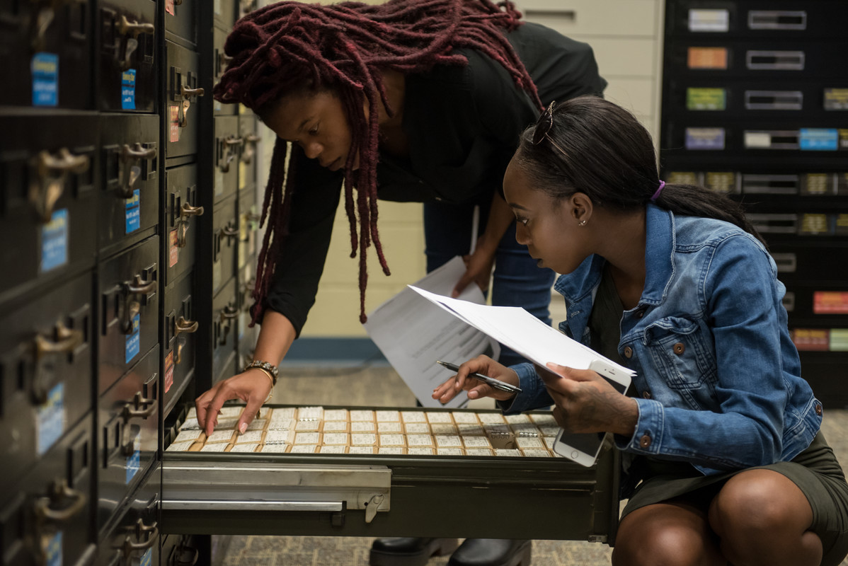 two students looking through a shelf of microfilm as they get ready to research the reels on a reader