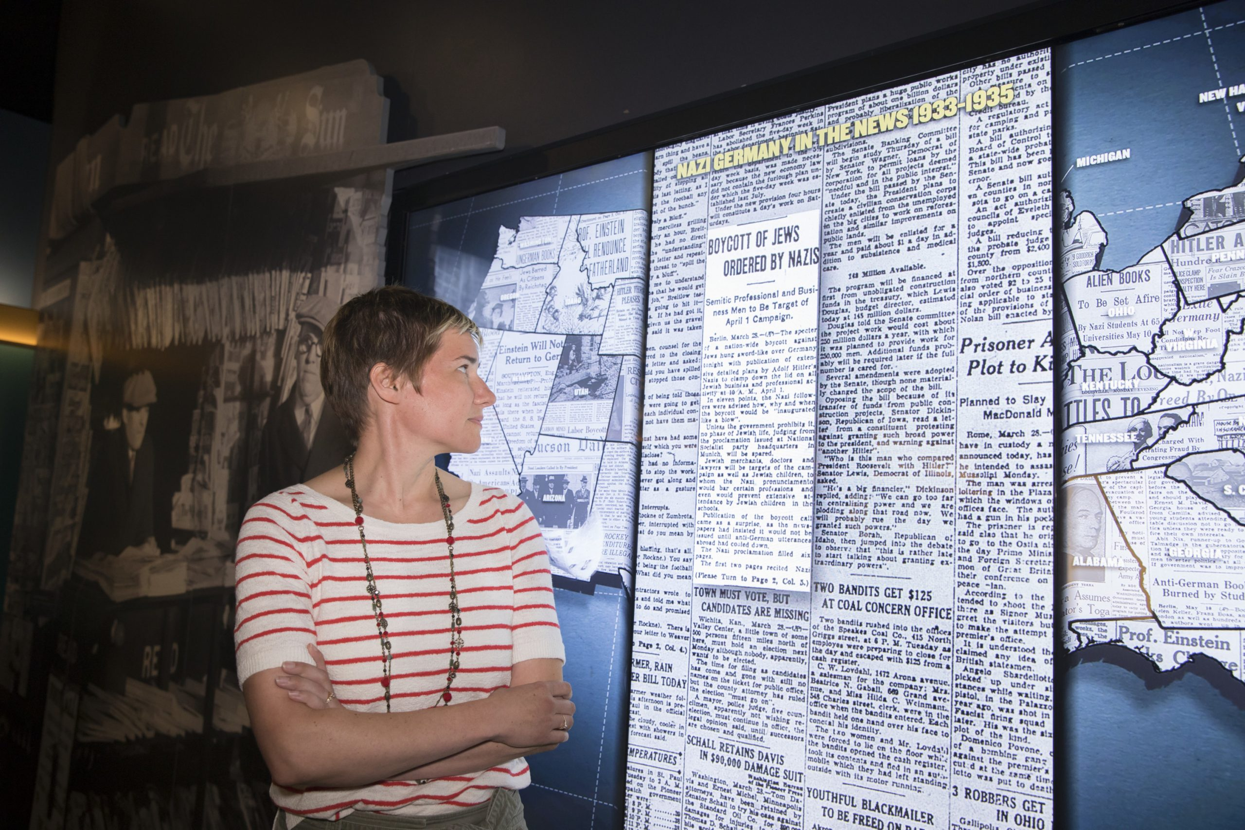 teacher looking at a large interactive map display of newspaper reporting on the Holocaust at the United States Holocaust Memorial Museum.